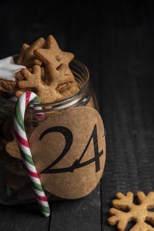 Paper tag with the number twenty-four on a glass jar full with homemade gingerbread cookies and a red-green stripped candy cane