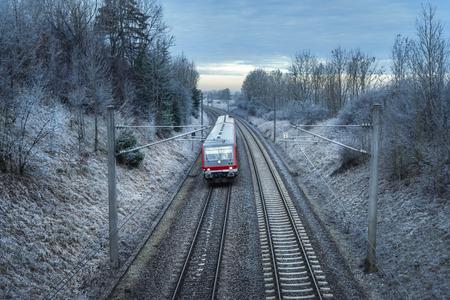 Foto de German passenger train traveling through snowy nature and frozen trees, at sunrise. Winter travel context. Modern public transportation. - Imagen libre de derechos