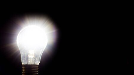 Photo for Glowing yellow light bulb, business idea concept.  Light bulb on black background with copy text. Light bulb on black background. The light bulb is a symbol of ideas, innovations, and new thoughts. - Royalty Free Image