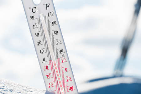 Photo for The thermometer lies on the snow and shows a negative temperature in cold weather on the blue sky.Meteorological conditions with low air and ambient temperatures.Climate change and global warming - Royalty Free Image