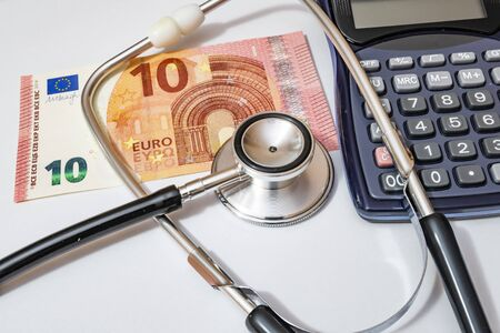 Photo pour close up currency paper banknote on white background with stethoscope and calculator. - image libre de droit