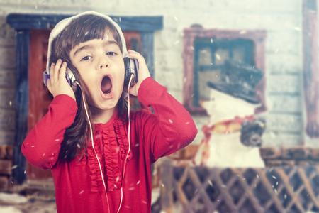 Adorable girl wearing a Santa hat listening to music and singing Christmas carols.
