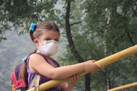 girl in a breathing mask in a smoke-filled backyard