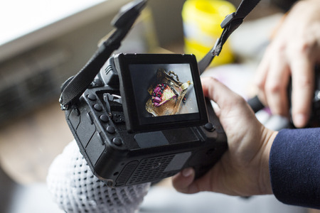Photo for cake photo on the camera screen. the girl holds the camera in hand. - Royalty Free Image