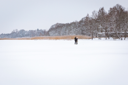 Photo pour Riga, Latvia, Juglas lake. Two persons stay at lake in winter. Snow and fresha air. Love. 2016 - image libre de droit