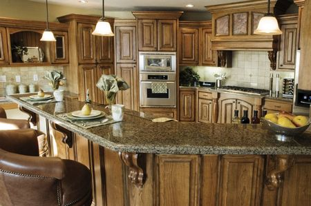 The interior of a rustic country kitchen featuring an elegant stove with built-in wooden cabinetry and marble countertops