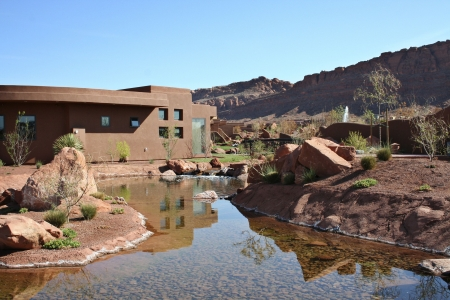 A beautiful modern home built in a desert landscape with waterfall and a pond and the red rock cliffs in the background