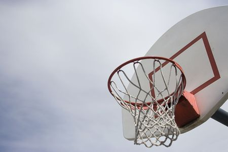 An outdoor basketball basket with the simple backdrop of a cloudy day. Lots of Copy space