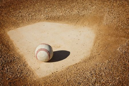 A baseball sitting on home plate. Great sports background