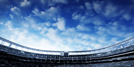 Wide Horizontal photo of a american football stadium with blue clouds in the sky
