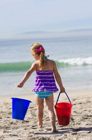 Cute little girl busy building sand castles on the beach