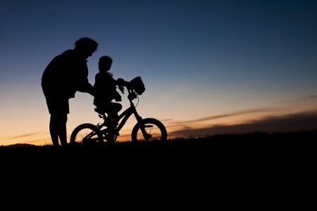 Parent helping a child Learn to Ride A bike