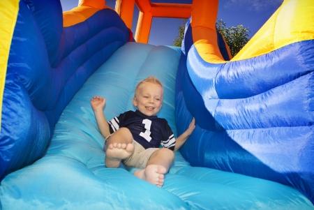 Photo pour Boy sliding down an inflatable Side  - image libre de droit