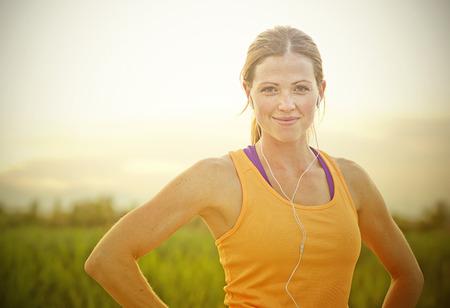 Foto de Smiling Female Jogger at Sunset with sun flare - Imagen libre de derechos