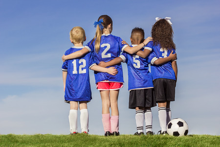 Diverse group of boys and girls soccer players standing together with a ball against a simple blue sky backgroundの写真素材
