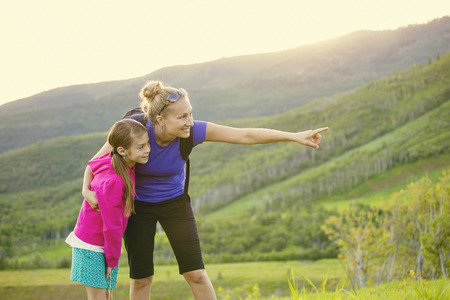Foto de Family hiking in the mountains together. Young mother pointing out wildlife while she and her daughter take a hike together in the mountains on a beautiful summer evening - Imagen libre de derechos