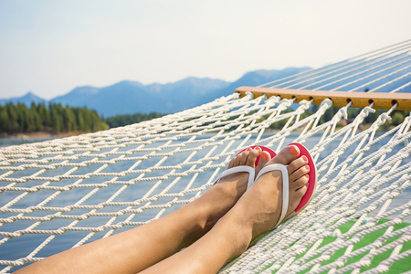 Photo for Woman relaxing in a hammock on a beautiful Mountain Lake - Royalty Free Image