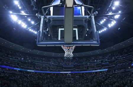 Brightly lit Basketball backboard in a large sports arena.