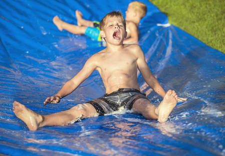 Photo pour Excited little boys playing on a slip and slide outdoors - image libre de droit