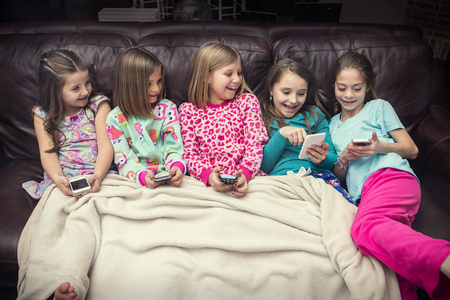 Group of cute, happy little girls playing with their smart phones together while sitting on the couch at a sleepover. Five girls all connecting to social media and reacting together to funny content