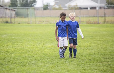 Foto de Two soccer teammates walking off the field after a loss. Concept photo of encouragement from friends after disappointment from a loss - Imagen libre de derechos