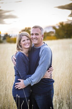 Photo pour A Beautiful Middle-Aged Couple portrait outdoors. Smiling and looking at the camera with a happy expression on their faces as they hold each other with love - image libre de droit
