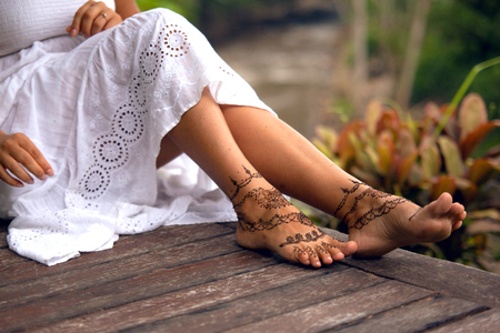 Henna tattoo design on legs. Beautiful indian mehendi ornaments painted on a body part.の写真素材