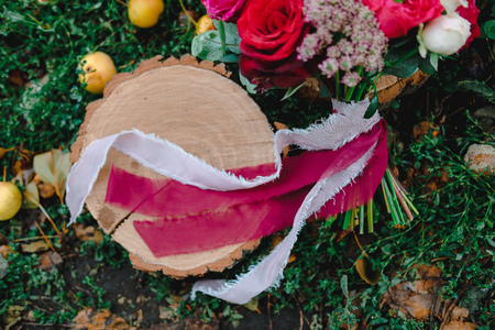 Foto de Wedding bouquet with red and white roses of different varieties in autumn colors lying on wooden saws on grass among fallen apples in garden. - Imagen libre de derechos