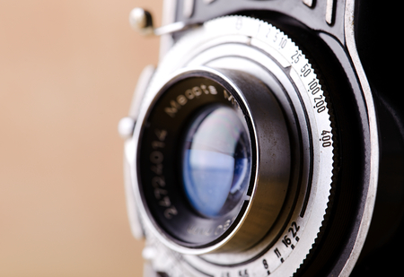 Horizontal photo with detail of lens of old camera. Picture contains detail of metal set up wheel for shutter speed.