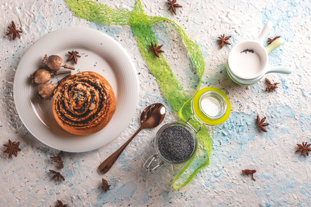 Horizontal photo with top view on sweet rolled bun stuffed by poppy. Bun is on white plate with few poppyheads. Glass gar with poppy seeds and stacked small bowls are next to plate on light board.
