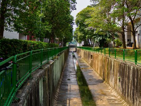Photo for Tree lined water canal channel in a HDB residential housing estate in Singapore.  - Royalty Free Image