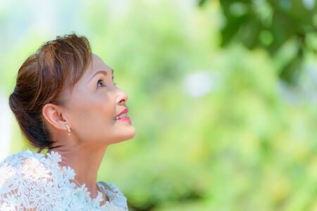 Photo pour Closeup side face of a healthy Asian middle-aged woman dress in Thai style clothes, Portrait old lady resting outdoors looking up smiling happy in the park, copy space on green tree nature background - image libre de droit