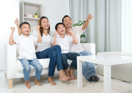 Foto de Asian family watching television and shouting on their home side in a sporting competition - Imagen libre de derechos