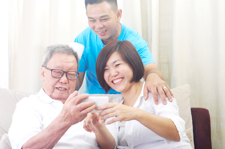 Photo pour Modern technology, age and people concept. Asian senior man with his daughter and son taking selfie, using smartphone, self photographing - image libre de droit