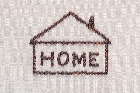 Photo pour Home letter sign enclosed in house shape, made from roasted coffee beans isolated on creamy linea canvas, shot close up. - image libre de droit