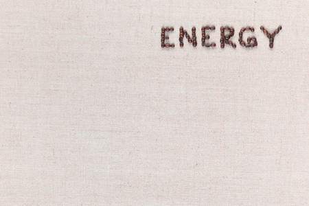 Foto de Energy word made with capital letters from roasted coffee beans on creamy linen canvas, shot from above, aligned top right. - Imagen libre de derechos