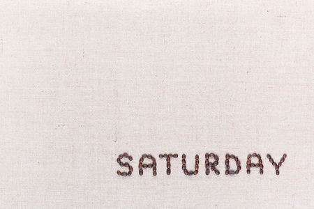 Photo for The word Saturday written with coffee beans on creamy linea canvas, shot from above , aligned at the bottom right. - Royalty Free Image