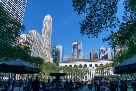 New York, United States - May 12, 2018 : People enjoying a spring day in Bryant Park in New York City, NY. Bryant Park is a 9,603 acre privately managed park in the center of Manhattan