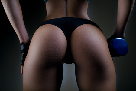 Foto de Sexy fitness buttocks close-up. Part of fitness body on a black background. Perfect female sports buttocks. Fitness woman posing in the studio. - Imagen libre de derechos