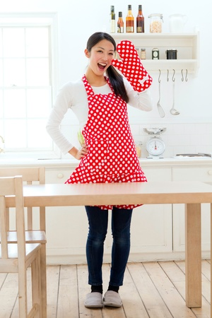 Beautiful apron woman in the kitchen の写真素材