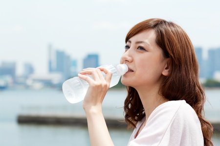 Beautiful young woman drinking waterの写真素材