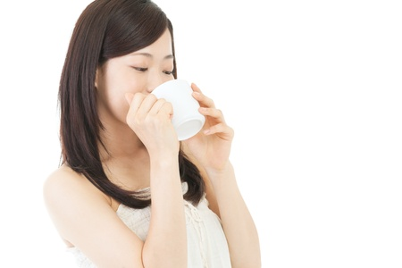 Beautiful asian woman drinking coffee on white backgroundの写真素材