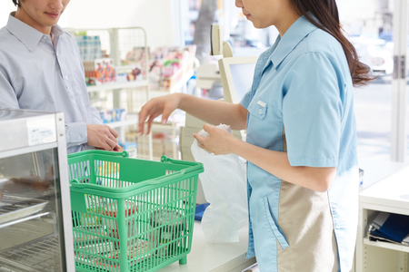 Young female cashier helping a customer pay