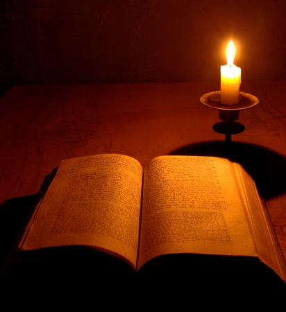 antique bible on jewish with candle on wooden table