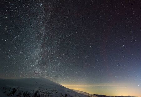 Photo pour The starry magical sky with pink haze is located above the winter ski resort. The concept of a country vacation and enjoyment of pristine nature. Place for text - image libre de droit