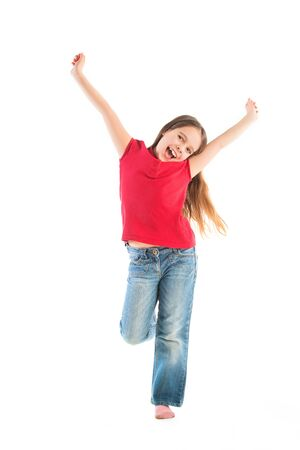 Photo pour Happy child posing in childrens clothes standing on one leg, arms raised up. - image libre de droit