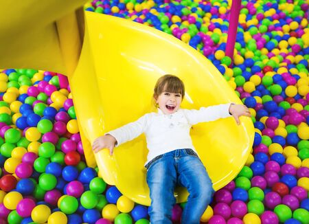 Photo pour Happy child having fun in the playroom. Girl in children's clothes posing sitting on her knees on a childrens slide - image libre de droit