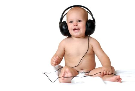 Photo pour Little one year old boy listens to music in big headphones and smiles on an isolated white background - image libre de droit