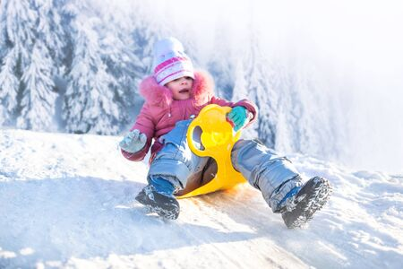 Photo for Happy small girl in winter clothing riding downhill on snow with winter snowy forest at background on frosty clear day. Winter family activities concept - Royalty Free Image