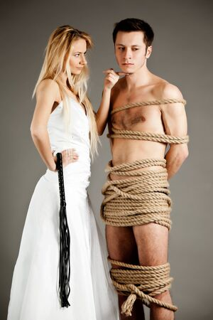 Photo pour Young woman in wedding dress standing near naked man tied up with ropes - image libre de droit